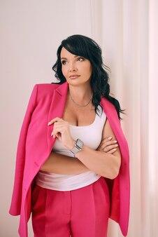 トレンディなフクシアピンクのスーツファッションのモダンなインテリアで美しいスタイリッシュな自信を持ってブルネット