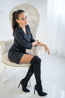 Beautiful stylish confident woman sitting in a white chair in the studio