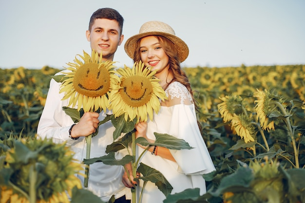 Beautiful and stylish couple in a field with sunflowers