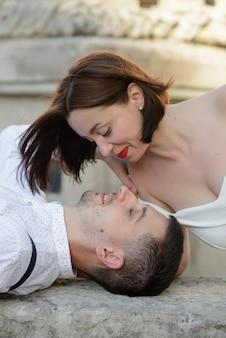 旧市街の屋外でデートにキスする美しいスタイリッシュなカップル。