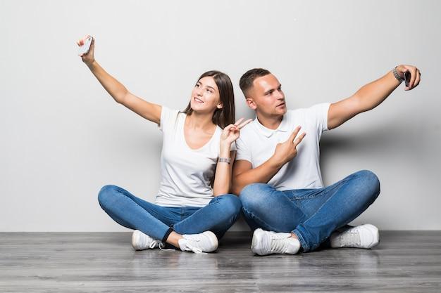 白い背景で隔離の自分撮りを一緒に作る美しいスタイリッシュなカップル