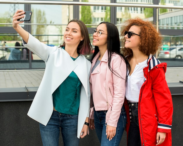 Beautiful stylish female friends taking selfie in smartphone