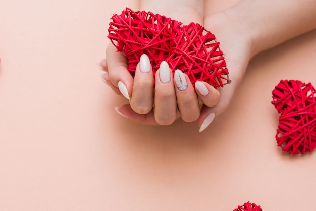 Beautiful stylish female manicure on a gray background with gift in hand.