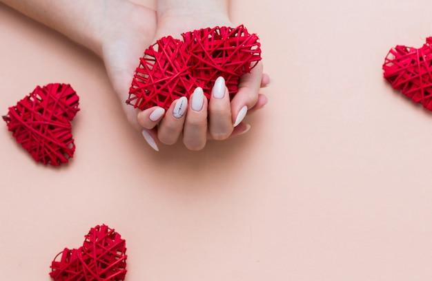 バレンタインの装飾が施されたピンクの背景に美しいスタイリッシュな女性のマニキュア