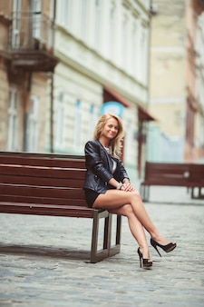 Beautiful stylish girl in a black leather jacket with dark lipstick and makeup in the city on the bench