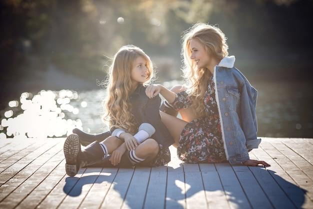 숲속의 산 호수 근처에 있는 아름다운 세련된 여자 친구, 데님 스타일. 행복한 어린 시절, 자매애 및 자연과의 일치에 대한 아이디어와 개념