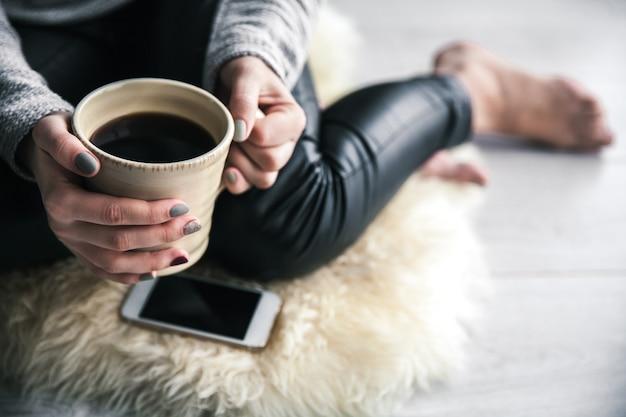 革のズボンとコーヒーと携帯電話で床に座っているモダンなセーターの美しいスタイリッシュな女の子