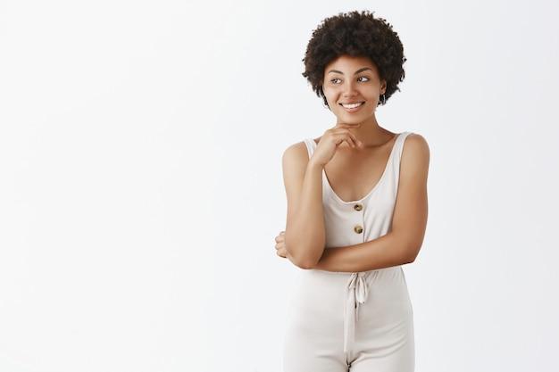 Bella ragazza alla moda in posa contro il muro bianco