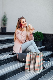 通りに座って、買い物をした後、コーヒーを手に持って、屋外でポーズをとる美しいスタイリッシュな女の子。