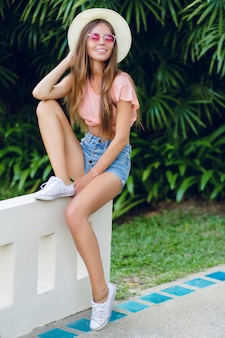 Beautiful stylish girl sitting on white fence in tropical park.