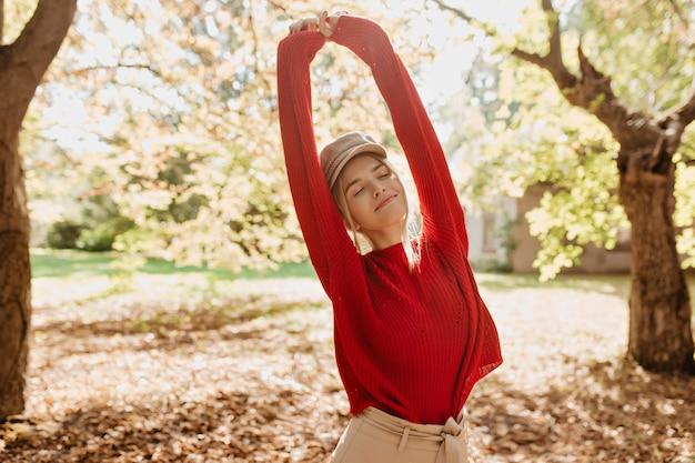 太陽の下で公園で笑っている美しいスタイリッシュな女の子。幸せな屋外を感じている赤いセーターの魅力的なブロンド。