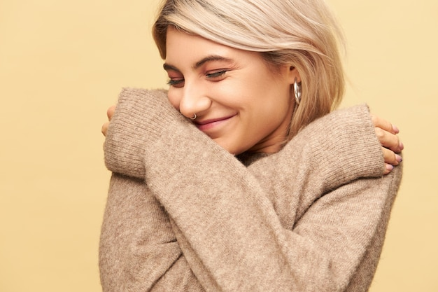 Beautiful stylish girl with facial piercing being in good mood posing isolated with arms crossed on her chest, wearing cozy cashmere sweater with long sleeves, warming up on cold december day