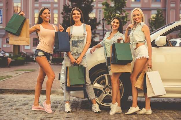Beautiful stylish girls are holding shopping bags.