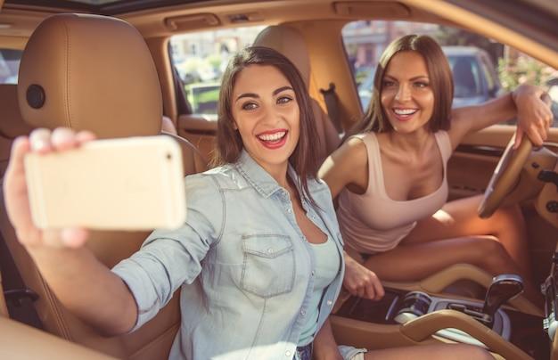 Beautiful stylish girls are making selfie using smartphone