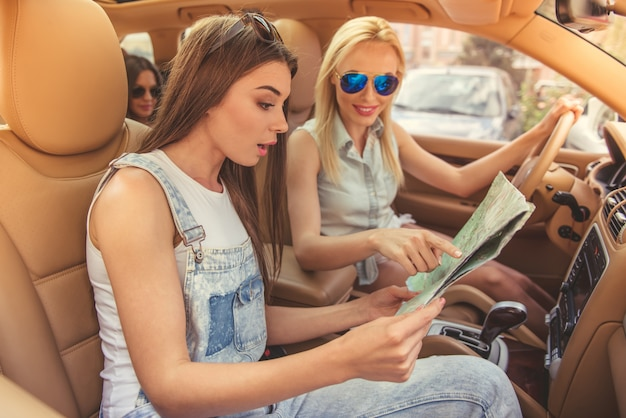 Beautiful stylish girls are studying the map.