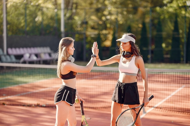Ragazze belle ed eleganti sul campo da tennis