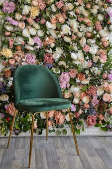 Beautiful stylish green chair stands against a decorative wall made of multi-colored flower buds