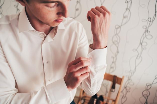 Красивый стильный жених застегивает кнопку крючка на рубашке