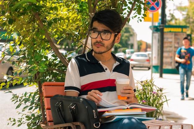 コーヒーのグラスを保持し、本とベンチに座ってメガネの美しいスタイリッシュな男