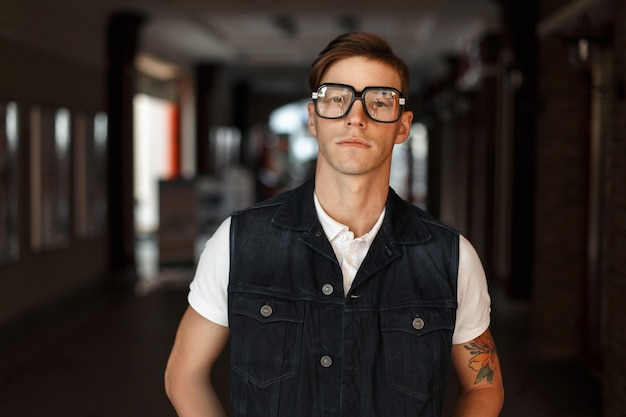 入れ墨とヴィンテージメガネの美しいスタイリッシュな流行に敏感な男