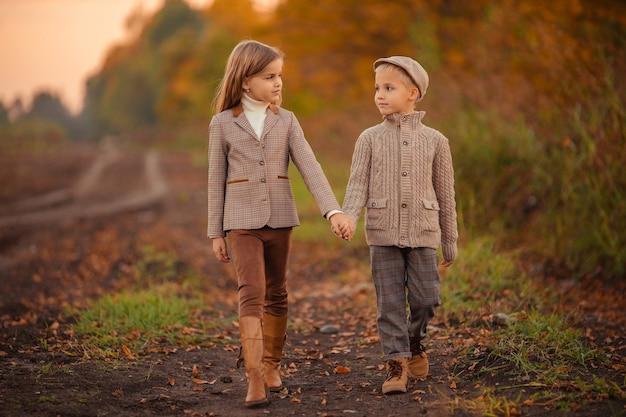 Красивые стильные дети брат и сестра осенью на прогулке в парке