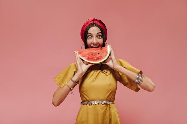 赤いバンダナ、モダンなブレスレット、カメラを見てスイカを食べる黄色の明るいドレスの美しいスタイリッシュな女性