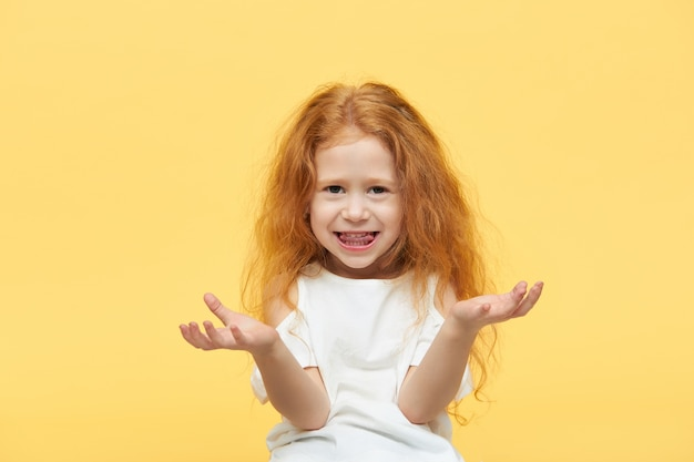 보이지 않는 물건을 들고있는 것처럼 그녀의 앞에서 열린 손바닥을 유지하는 긴 생강 머리를 가진 아름다운 세련된 어린 소녀