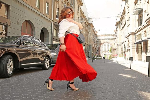 通りにバッグを持つ美しいスタイリッシュな太りすぎの女性