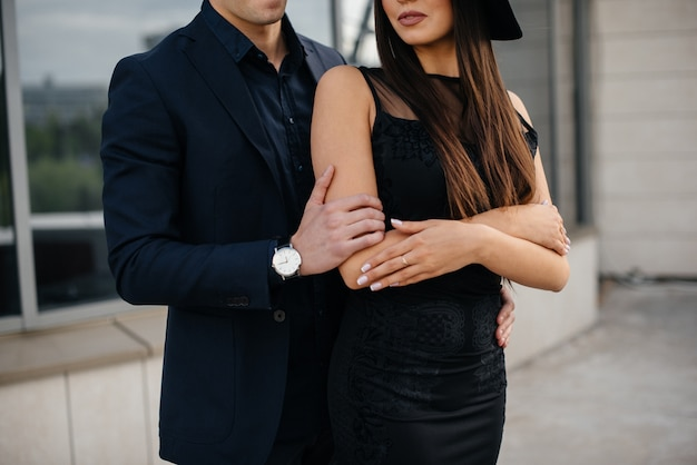 A beautiful, stylish pair of young people in black clothes and glasses stand against the background of an office building in the sunset. fashion and style