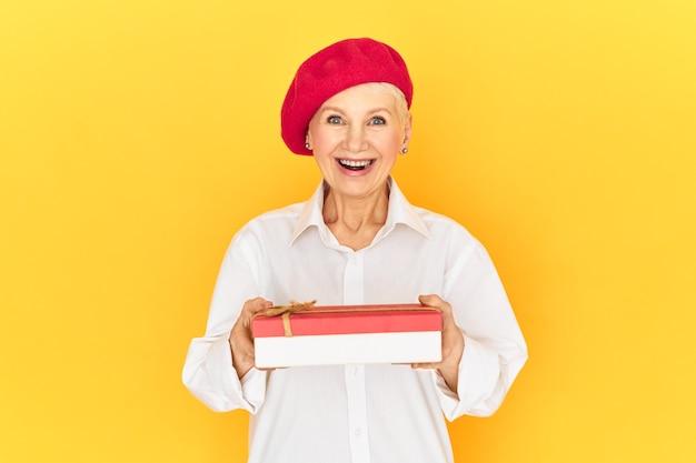 Bella ed elegante signora in pensione in camicia bianca e berretto rosso eccitata da una piacevole sorpresa, ricevendo una scatola di caramelle per la giornata internazionale della donna, aprendo la bocca con eccitazione