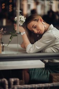 Красивая стильная романтическая молодая девушка в вечерней одежде и украшениях сидит, мечтает с цветком в руке в кафе. фото высокого качества
