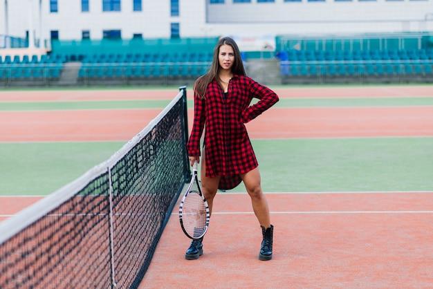 테니스 코트에 검은 유행 운동복에 아름 다운 세련 된 섹시 한 여자.