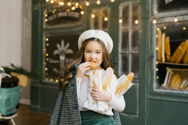 A beautiful, stylish six-year-old girl holds a bag of baguettes in her hands and stands near the window of a bakery with fresh pastries. she breaks a loaf of bread and eats it