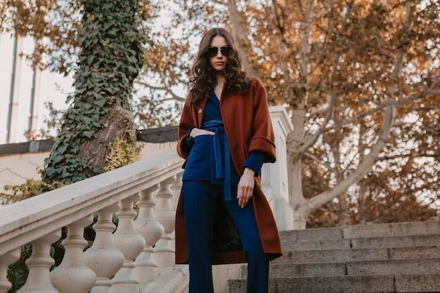 따뜻한 갈색 코트와 파란색 정장을 입고 거리 계단을 걷고 곱슬 머리를 가진 아름 다운 세련 된 미소 마른 여자, 가을 유행 패션 거리 스타일