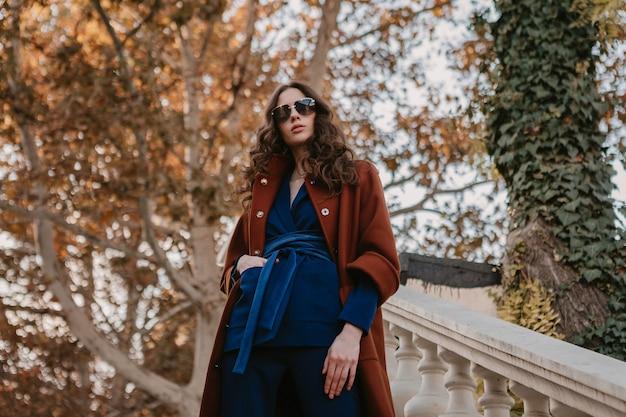 Bella donna magra sorridente alla moda con capelli ricci che cammina nelle scale della strada vestita in cappotto marrone caldo e abito blu, stile di strada moda alla moda autunno