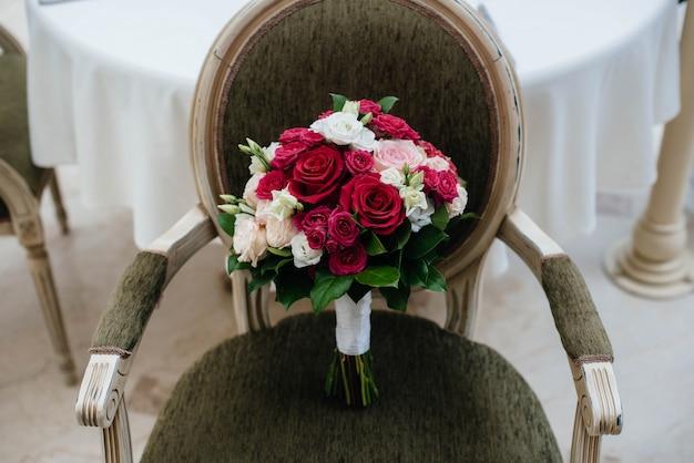 椅子の上の美しいスタイリッシュなウェディングブーケのクローズアップ。結婚式の植物学。
