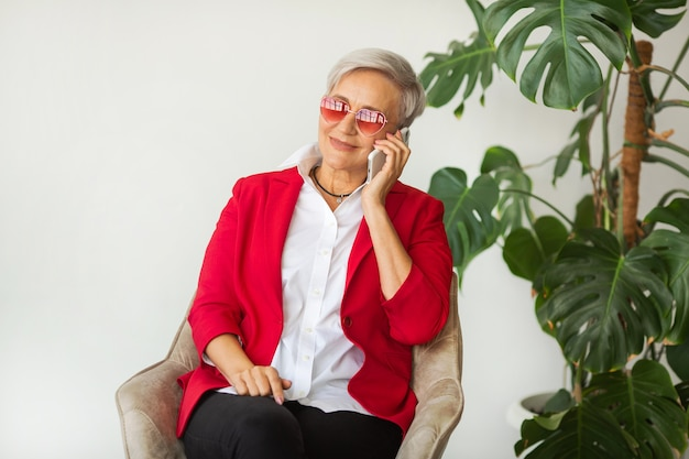 サングラスをかけた携帯電話と赤いジャケットで老化した美しいスタイリッシュな女性