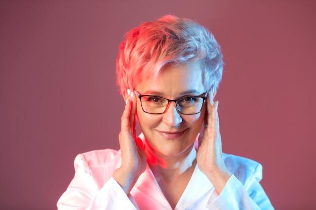 Красивая стильная женщина в возрасте в очках, в белом пиджаке