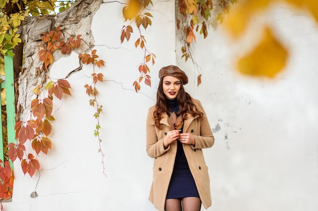 Beautiful stylish woman dressed in beige coat and brown beret is standing in front of the white ancient wall.