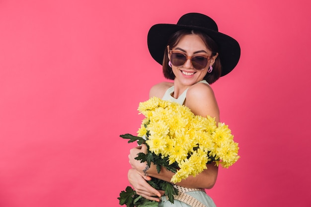 Beautiful stylish woman in hat and sunglasses posing, holding large bouquet of yellow asters, spring mood, positive emotions isolated space