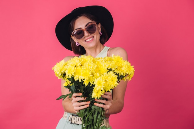 Beautiful stylish woman in hat and sunglasses posing, holding large bouquet of yellow asters, spring mood, positive emotions isolated
