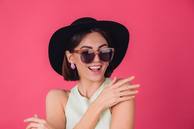 Beautiful stylish woman in hat and sunglasses posing over pink red wall