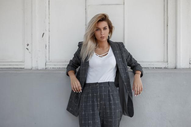 세련 된 회색 비즈니스 정장에 아름 다운 세련 된 여자는 거리에서 벽 근처 의미합니다. 비즈니스 패션 레이디