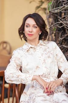 屋外のカフェに座っているベージュのドレスで美しいスタイリッシュな女性。オープンエアのカフェで幸せな女性の肖像画