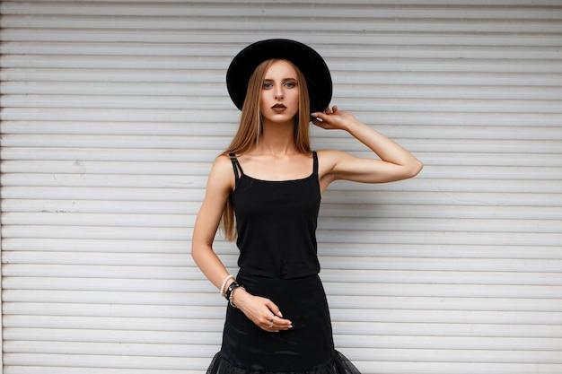 白い壁の近くに帽子をかぶった黒いファッションの服を着た美しいスタイリッシュな女性