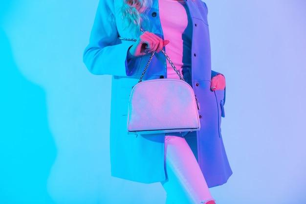 ネオンピンクの光のスタジオで白いファッショナブルなハンドバッグと色付きの青いブレザー、ブラウス、ジーンズの美しいスタイリッシュな女性。革製の女性用バッグのクローズアップ