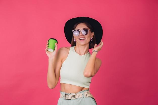 ポーズをとって、アクティブな動く幸せな前向きな感情を踊るコーヒーの紙コップを保持している帽子とサングラスの美しいスタイリッシュな女性、