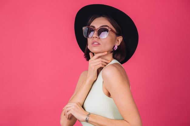 Красивая стильная женщина в шляпе и солнцезащитных очках позирует