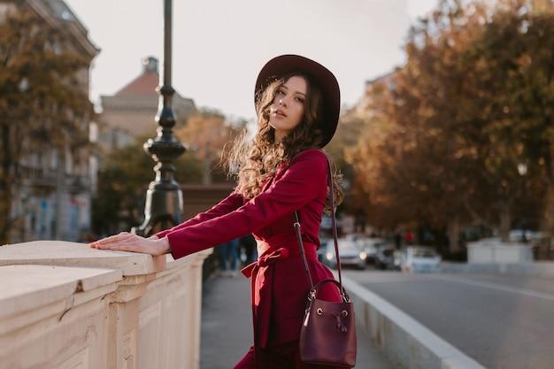 Красивая стильная женщина в фиолетовом костюме гуляет по городской улице, модная тенденция сезона весна-лето-осень в шляпе, держа кошелек