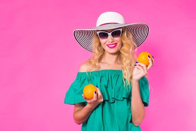 Красивая стильная женщина в солнцезащитных очках и шляпе с апельсинами веселится на розовом